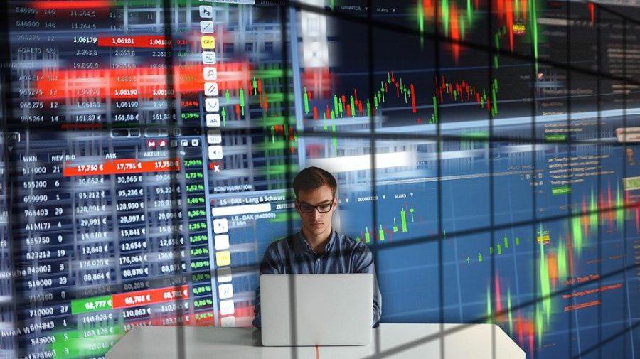 Man Sitting at a Computer with Charts